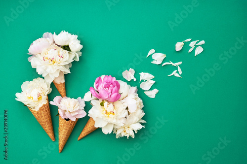 Foto Murales Ice cream cones with white peony flowers on green background. Summer concept. Copy space, top view