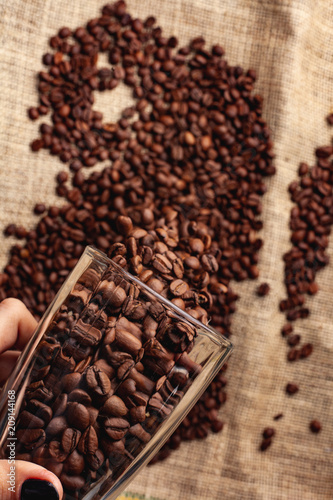 Fotobehang Koffiebonen Coffee grains are poured from a glass