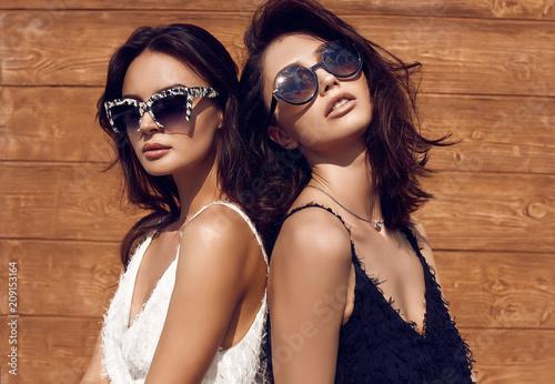 Wspaniała jasna para brunetka kobiet w czarno-białe sukienki