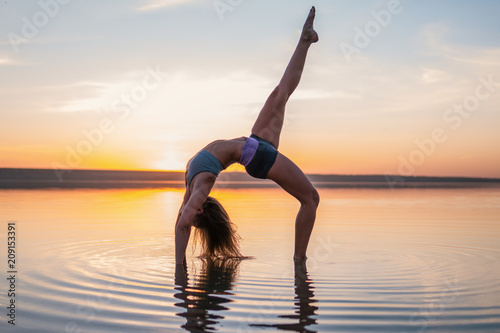 Fototapeta woman on the beach at sunset doing yoga asana. Morning natural stretch warm-up training