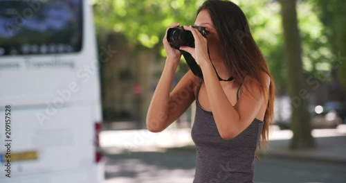 Sticker Pretty millennial tourist standing on street taking picture with dslr camera, Creative young woman wearing striped tank top taking fun photo, 4k