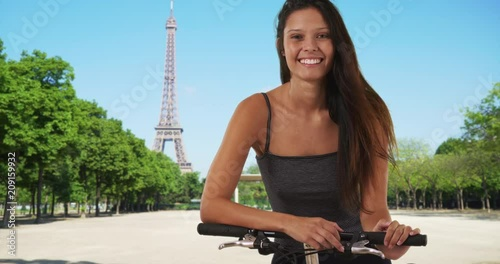 Poster Pretty tourist woman with her bike in Paris, France on summer travel, Portrait of cheerful Caucasian girl in striped tank top cycling near Eiffel Tower, 4k