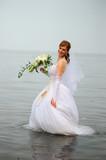 bride in wedding dress in water - 209163904
