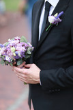 Caucasian groom wearing black suit and tie keeping bouquet of flowers. Concept of wedding. - 209169735