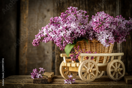 Foto Murales Beautiful composition with  bouquet of lilac in a wicker basket