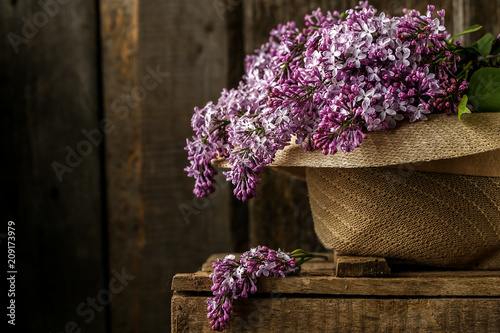 Beautiful composition with bouquet of lilac in old hat