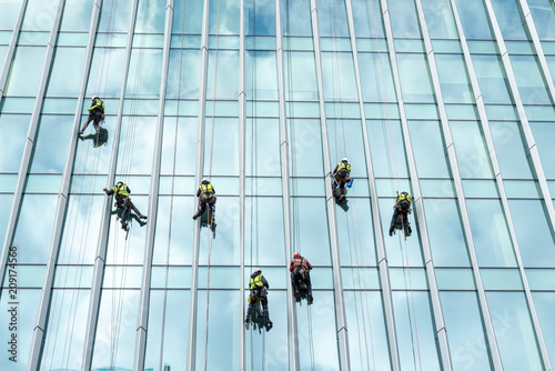 Window washers cleaning the glass facade of a skyscraper, high risk work.