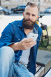 Young bearded man using mobile phone - 209174762