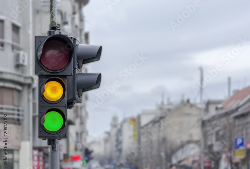 Foto Murales Green and yellow light semaphore on city urban with blury background
