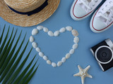 Shells, a sea ster, sneakers, a tropical leaf, a summer hat and camera on the sea blue background. Minimal summer. Hipster vibes - 209178139