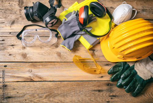 Leinwandbild Motiv Construction safety. Protective hard hat, headphones, gloves and glasses on wooden background, copy space, top view