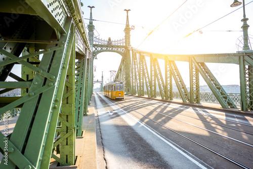 Widok na sławnym swoboda moscie z starym żółtym tramwajem podczas ranku zaświeca w Budapest, Węgry