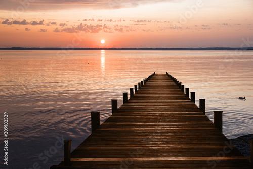 Holzsteg am See und romantischer Sonnenuntergang