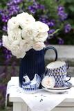 Dekoration mit Rosenstrauß, Kaffeetassen und Porzellanvogel in Weiß und Blau - 209187796