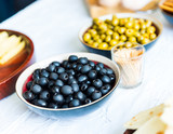 Black and green olives in bowls on white table - 209189398