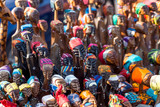 Wooden African figurines on display. The little figures have colourful headscarves. - 209192598