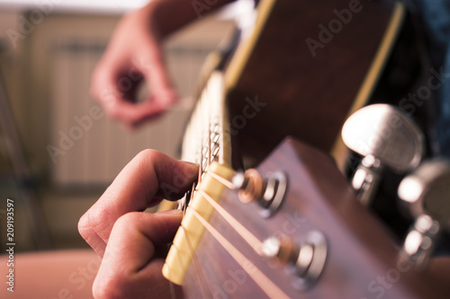 Female hand playing on acoustic guitar. Close-up. - 209193597