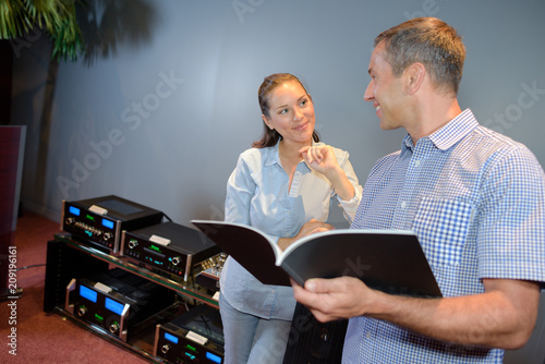 Man and woman with catalogue and electrical equipment