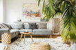 Quadro Pouf and wooden table in modern living room with painting above grey corner couch. Real photo
