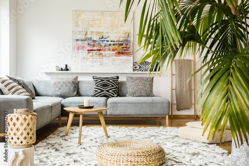 Leinwanddruck Bild Pouf and wooden table in modern living room with painting above grey corner couch. Real photo