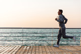 Side view of young running sportsman, during workout on quay, near the ocean. Full length. - 209203731