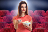 pretty young woman with pop-corn watching movie - 209205933