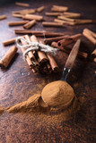 Cinnamon sticks and powder in spoon . - 209206132