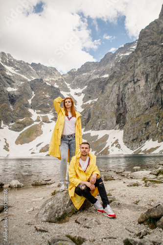 Aluminium Honing Young beautiful couple in yellow raincoats standing on a rock against a backdrop of a mountain lake in the Tatra National Park in Poland