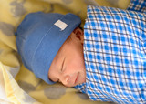Cute Eurasian newborn baby smiling in his sleep - 209209182