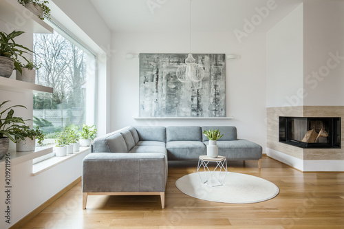 Leinwanddruck Bild Spacious white living room interior with grey corner couch, big modern art painting and fireplace