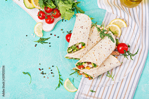 Burritos wraps with chicken and vegetables on light  background. Chicken burrito, mexican food. Top view, flat lay - 209213356