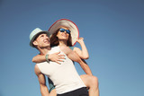 Beautiful young happy couple on blue sky background. - 209213568