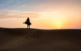 Woman in the desert with sunset view - 209214552