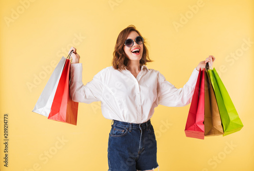 Portrait of young joyful lady in sunglasses standing with colorful shopping bags in hands on over pink background. Happy woman standing in white shirt and denim shorts