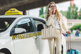 smiling blonde woman in eyeglasses talking by smartphone while standing with suitcase near taxi cab - 209217786