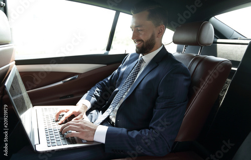 Fridge magnet Businessman working with laptop sitting in car