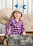 cute little girl in hat sitting in big old chest - 209219963