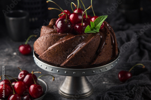 delicious chocolate bundt cake with fresh cherry on dark background