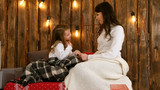 Mom and daughter are happily talking and holding hands at Christmas time - 209226186