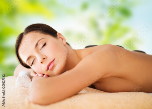 wellness, spa and beauty concept - beautiful woman having hot stone therapy over green natural background © Syda Productions