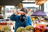woman with obscured face by camera taking picture in shop - 209227509
