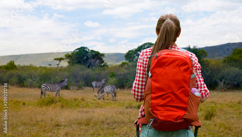 Leinwanddruck Bild adventure, travel, tourism, hike and people concept - young woman with backpack over zebras in african savannah background