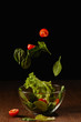Leinwanddruck Bild - Tomatoes and salad leaves falling in bowl above wooden table surface