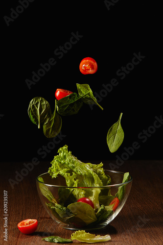 Leinwanddruck Bild Tomatoes and salad leaves falling in bowl above wooden table surface