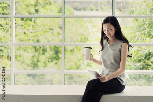 Young Asian smiling woman is drinking coffee in a cafe and holding a tablet computer in hands.