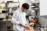 cooking food, profession and people concept - happy male chef cook with knife chopping carrot on cutting board at restaurant kitchen - 209235584