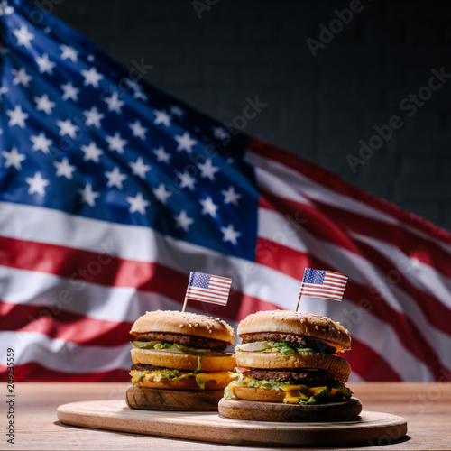 tasty burgers on wooden cutting board in front of waving united states flag - 209235559