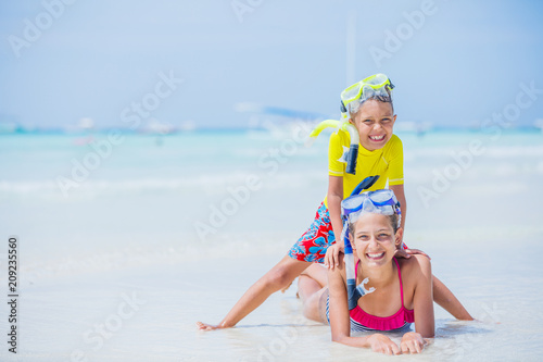 Brother and sister playing on the beach during the hot summer vacation day.