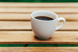 White Coffee Cup On Wooden Table In Green Garden