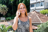 Female tourist with red hair talking with friend at phone - 209240920